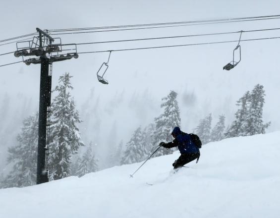 A skier shreds soft snow on Chair 6.